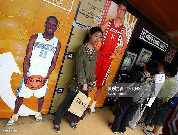 A young girl poses for pictures with the portraits of NBA stars Yao Ming and Earl Boykins beside scales showing their statures in the NBA Jam Van on...