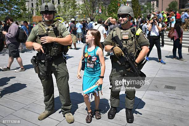A young girl poses with armed police near the sight of the Republican National Convention in downtown Cleveland on the second day of the convention...