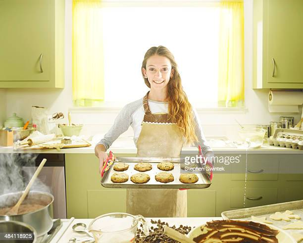 Young girl posing with tray of fresh cookies