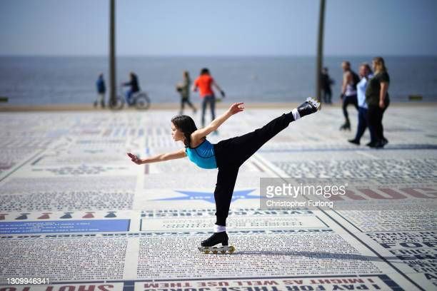 Young girl practices her skating skills in the Spring sunshine on Blackpool promenade as parts of the UK are set to see the warmest day of the year...