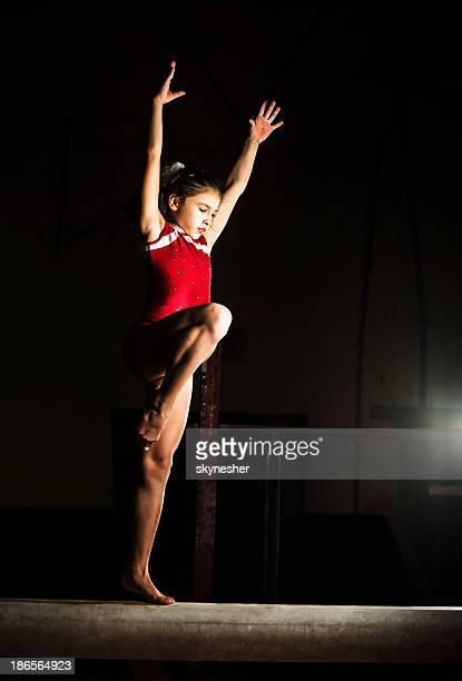 young girl practicing beam routine. - little girls doing gymnastics stock photos and pictures