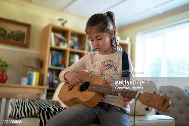 young girl practicing guitar, domestic life in england. - messing about stock pictures, royalty-free photos & images