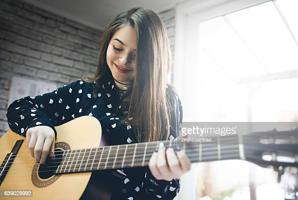 young girl  practicing guitar. - tocar - fotografias e filmes do acervo
