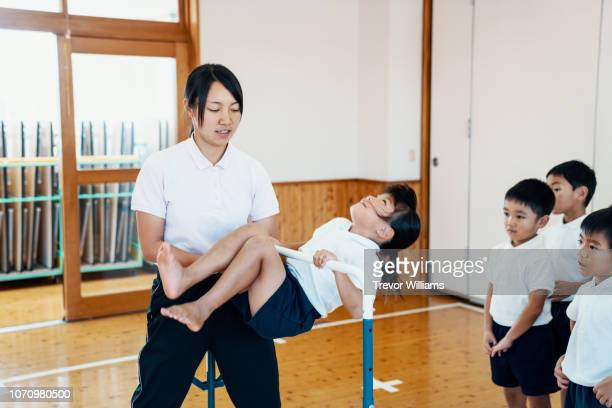 young girl practicing gymnastics at preschool in japan - artistic gymnastics stock pictures, royalty-free photos & images