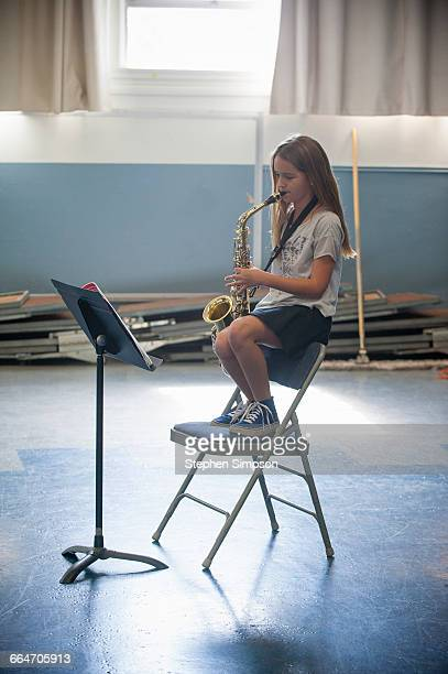 young girl practicing her saxophone