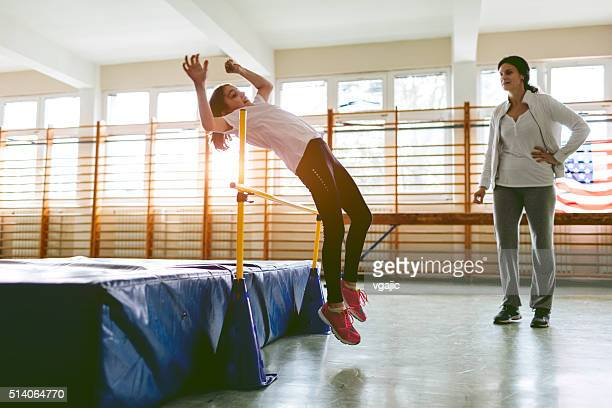 young girl practicing high jump indoors. - women's field event stock pictures, royalty-free photos & images