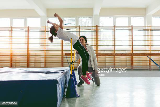 young girl practicing high jump indoors. - high jump stock pictures, royalty-free photos & images