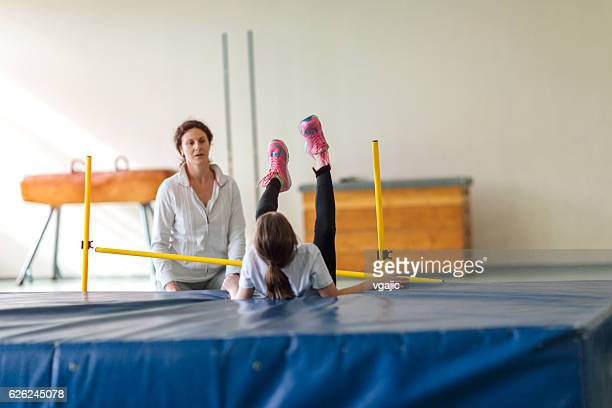 Young Girl Practicing High Jump Indoors.