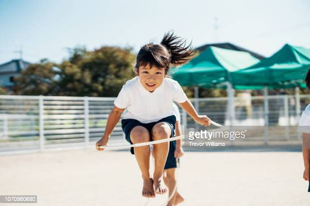 young girl practicing jump rope at preschool - sports uniform stockfoto's en -beelden
