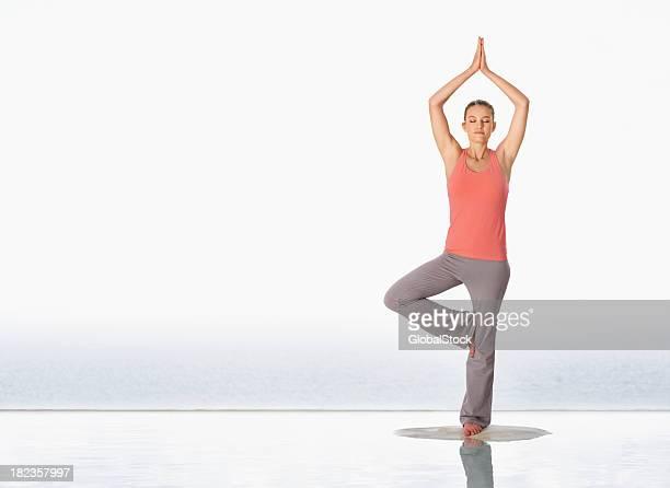 Jeune fille pratiquant le yoga sur la plage