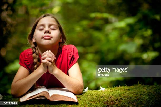 Young girl praying on a tree outdoors