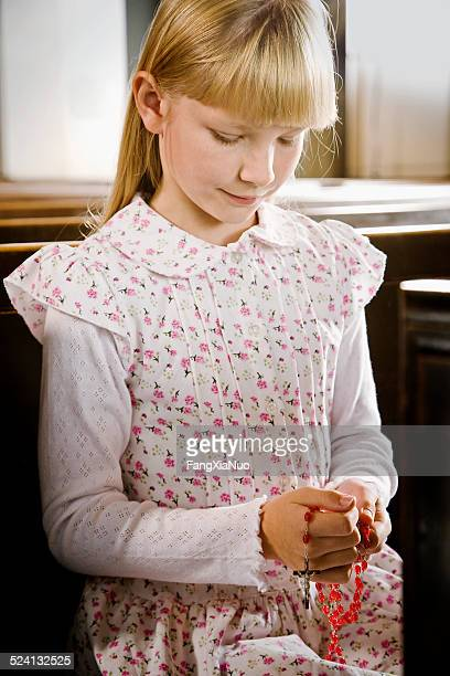 Young Girl Praying Rosary in Church