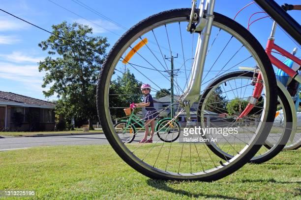 young girl preparing to go on a family bike ride. - rafael ben ari stock-fotos und bilder