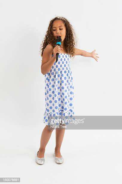 A young girl pretending to be a pop star