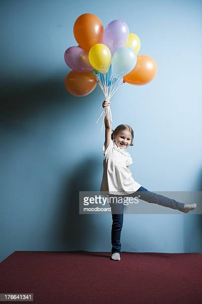 Young girl pretending to be lifted up by bunch of balloons