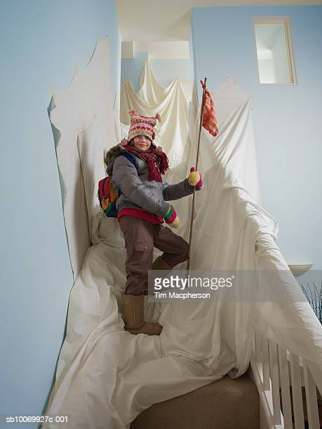 young girl (8-9) pretending to climb mountain on stairs at home - adventure stock pictures, royalty-free photos & images