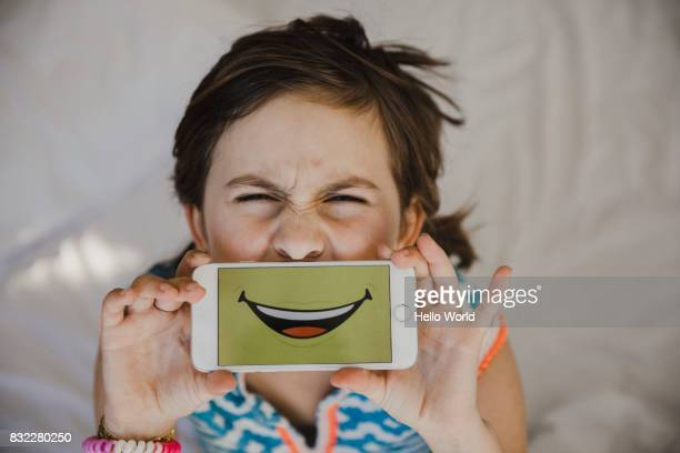 young girl pulling a funny face with smartphone over her mouth - nur kinder stock-fotos und bilder