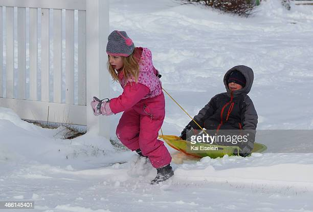 CONTENT] A young girl pulls a young boy on a plastic sled after a blizzard in Massapequa New York