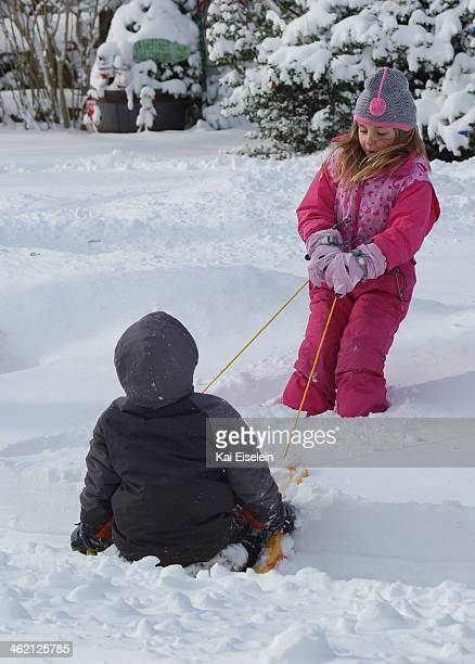 CONTENT] A young girl pulls a young boy through the snow on a sled after a blizzard in Massapequa New York