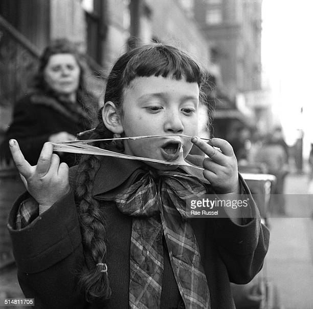 A young girl pulls her burst chewing gum bubble off of her face Brooklyn New York New York 1949