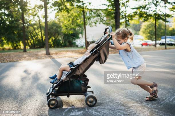 young girl pushing baby brother in stroller - pushchair stock pictures, royalty-free photos & images