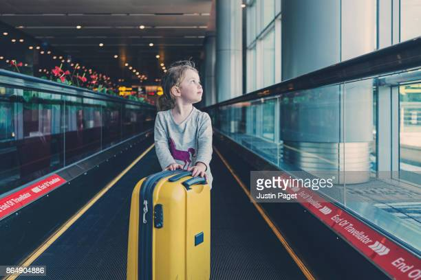 Young Girl pushing luggage through airport