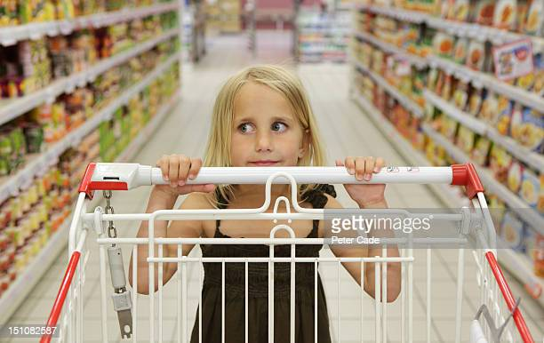 Young girl pushing trolley in supermarket aisle