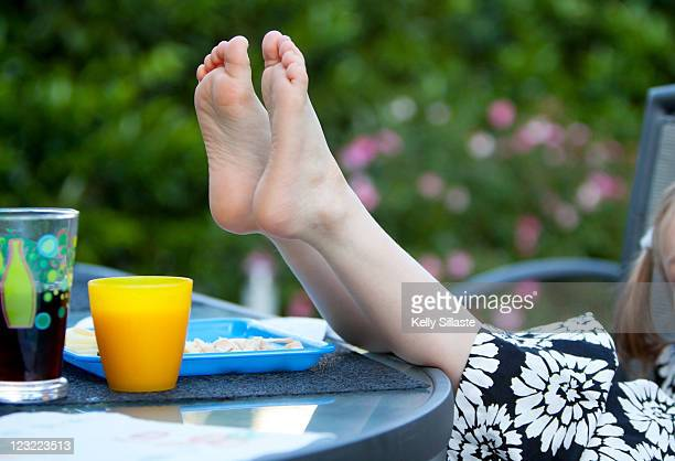 Young girl puts bare feet on table