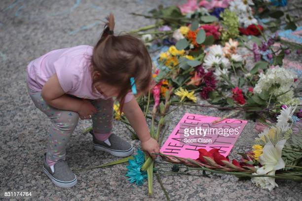 A young girl puts flowers on a memorial to Heather Heyer that was chalked on the pavement during a demonstration on August 13 2017 in Chicago...