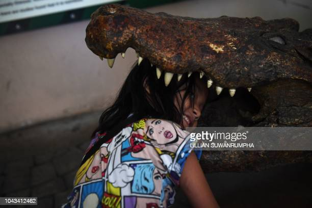 A young girl puts her head inside a taxidermised crocodile on the last day of opening at Dusit Zoo in Bangkok on September 30 2018 Dusit Zoo the...