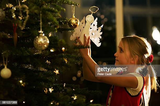 young girl putting angel on christmas tree - christianity stock pictures, royalty-free photos & images