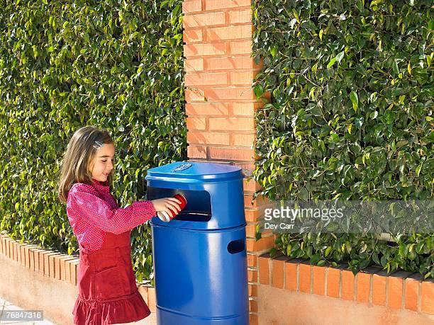 Young girl (5-7) putting can in public bin, Alicante, Spain,