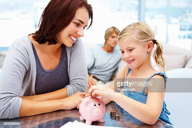 Young girl putting coins in piggy bank with mother watching