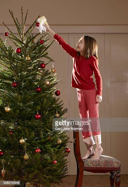 Young girl putting fairy on tree