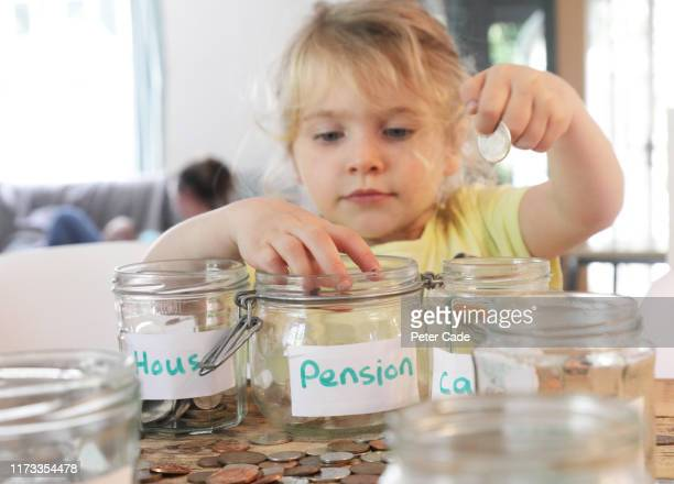 young girl putting money into savings jars - child stock pictures, royalty-free photos & images