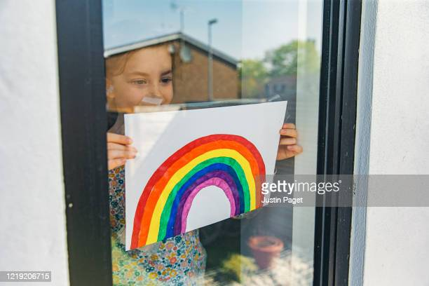 young girl putting rainbow drawing in window - drawing stock pictures, royalty-free photos & images