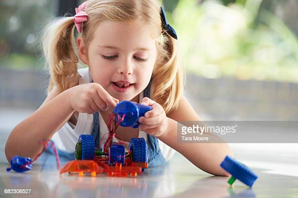 young girl putting together robot