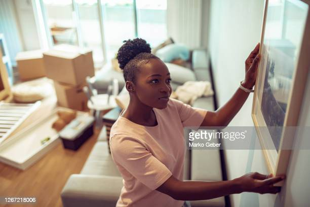 young girl putting up a painting in her new home - hanging stock pictures, royalty-free photos & images