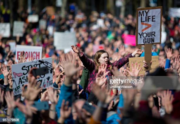 Young girl raises her hands with hundreds of others as Brandi Carlile performs at Seattle Center during the March for Our Lives rally on March 24,...
