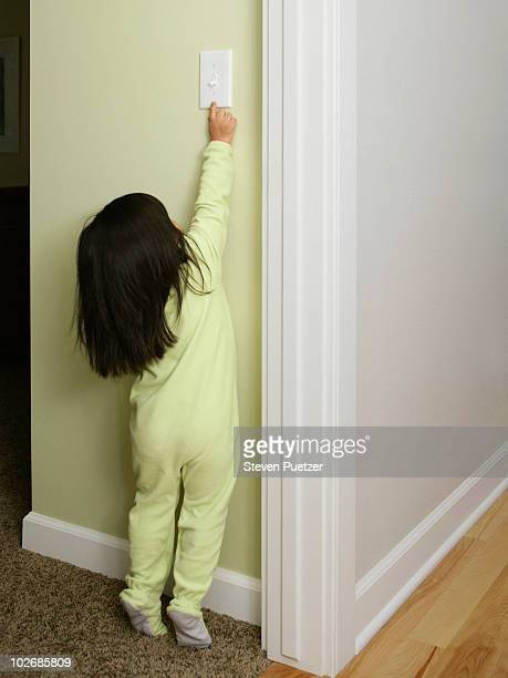 Young girl reaching for light switch