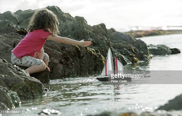 young girl reaching for toy boat in the sea - image focus technique stock pictures, royalty-free photos & images