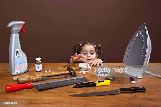 A young girl reaching onto a table of dangerous objects, studio shot