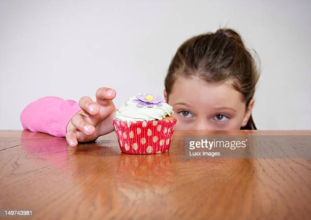 Young girl reaching over a table for cup cake