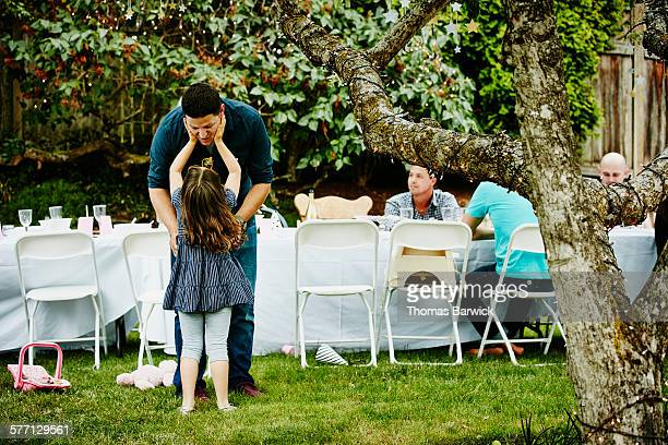 Young girl reaching up to father during party