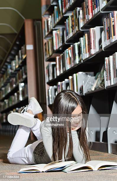 young girl reading a book in library - lying on front stock pictures, royalty-free photos & images