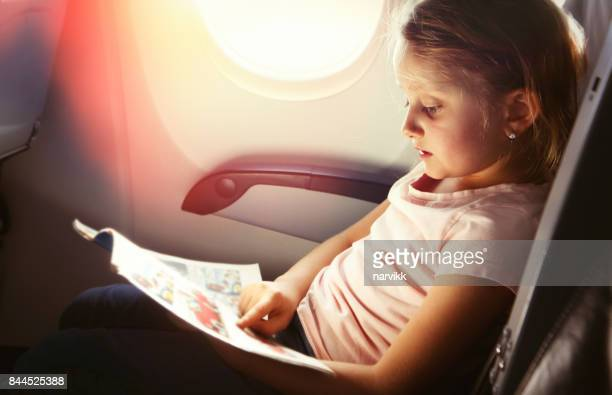 joven leyendo una revista en vuelo - revista publicación fotografías e imágenes de stock