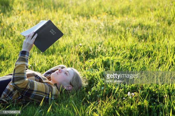 young girl reading bible in the meadow - bible stock pictures, royalty-free photos & images