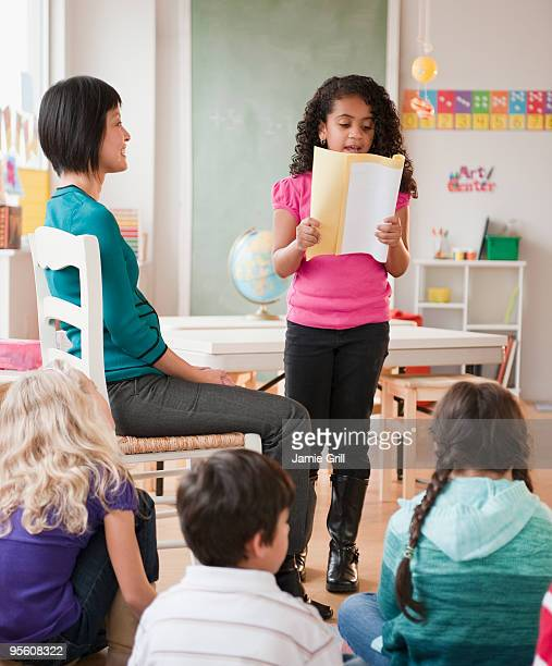 Young girl reading book report in front of class