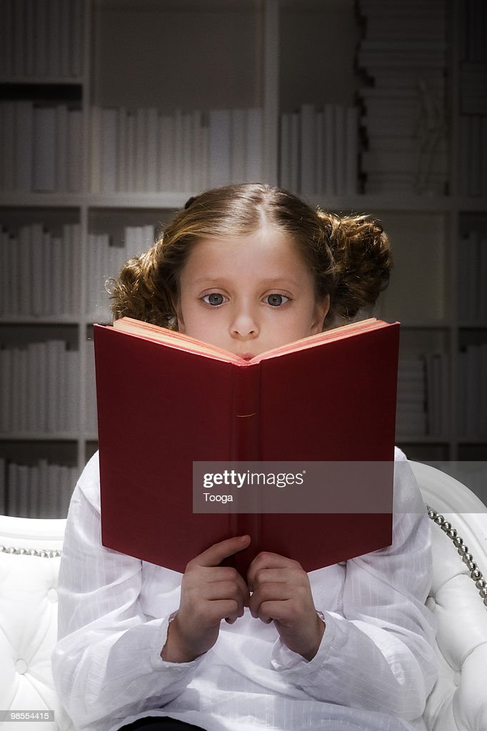 Young girl reading book with spotlit on both : Stock Photo