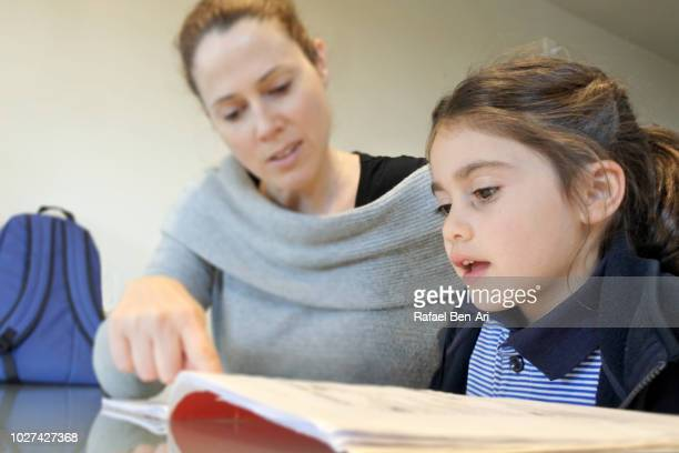 young girl reading her with the help of her mother - rafael ben ari ストックフォトと画像